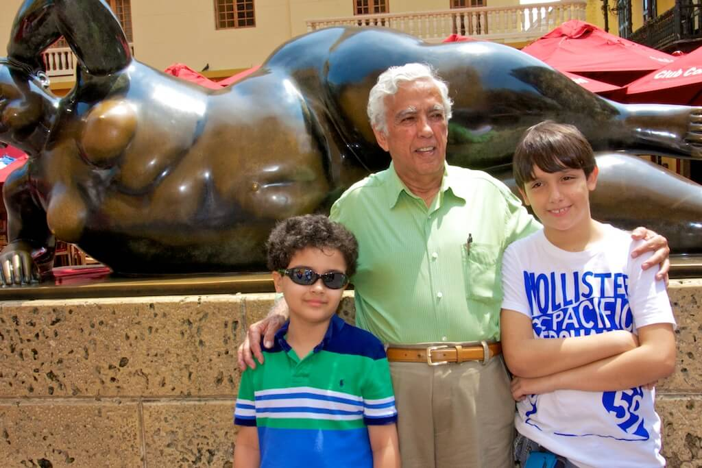 "Posing with grandpa and cousin before renowned Colombian painter and sculptor Fernando Botero's ""La Gorda"""